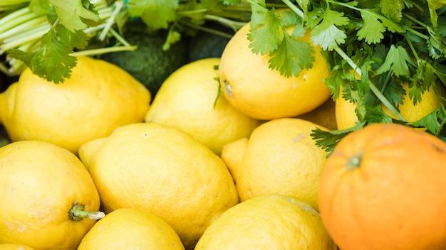 市場の屋台で新鮮なコリアンダーとジューシーレモンのクローズアップ