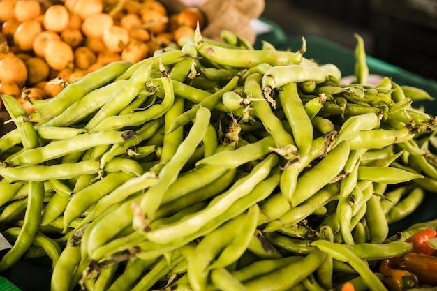 Куча овощей зеленого горошка на рыночных прилавках