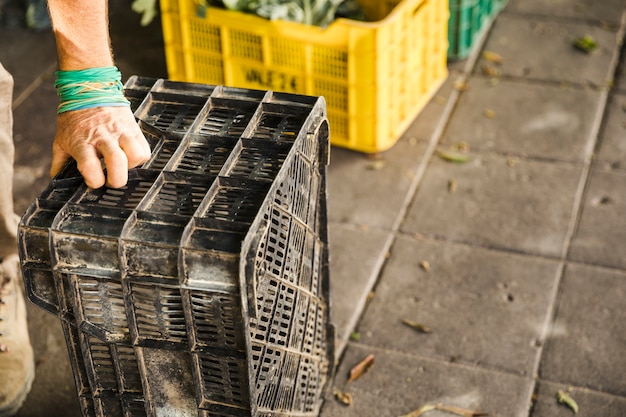 市場の場所で黒いプラスチック製の箱を持っている人間の手