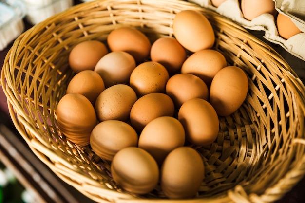 Органическое коричневое яйцо в плетеной корзине в супермаркете
