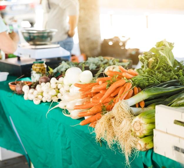 食料品店の市場での販売のためのテーブルの上の根野菜
