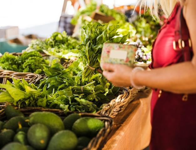 Самка выбирает здоровый листовой овощ на рынке
