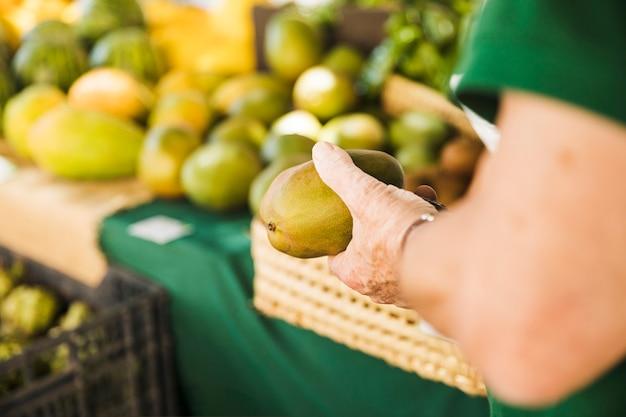 市場で生野菜を持っている男性の手のクローズアップ