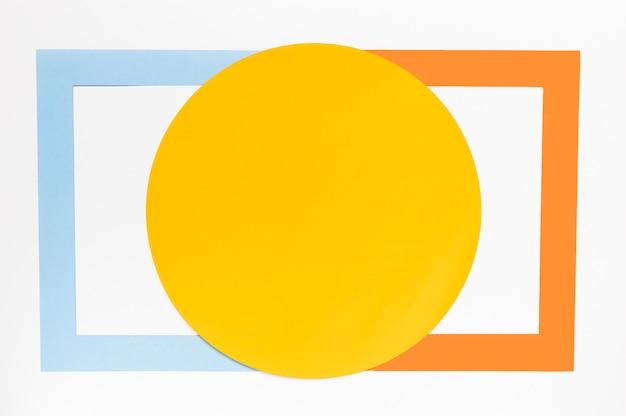 Вид сверху желтый круг с разноцветными геометрическими фигурами