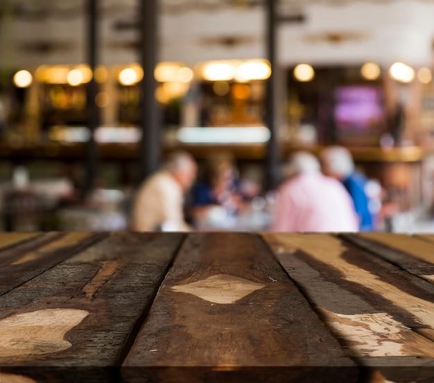 Деревянный стол с размытой сценой ресторана