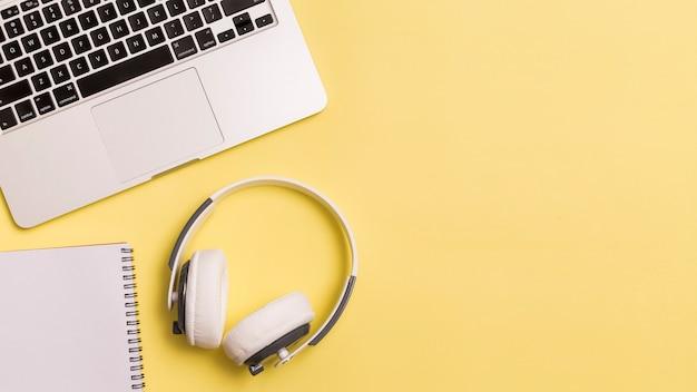 ノートパソコンと黄色の背景にヘッドフォン