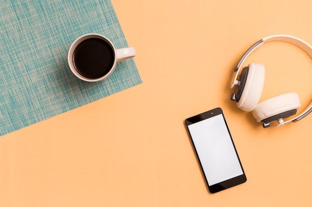 スマートフォンとオレンジ色の背景上のカップ付きヘッドフォン