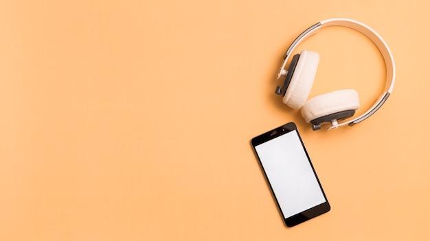 ヘッドフォンとオレンジ色の背景上のスマートフォン