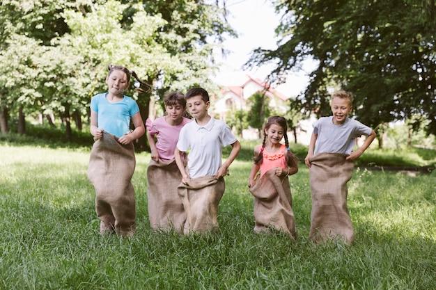 Дети вид спереди соревнуются в мешковины
