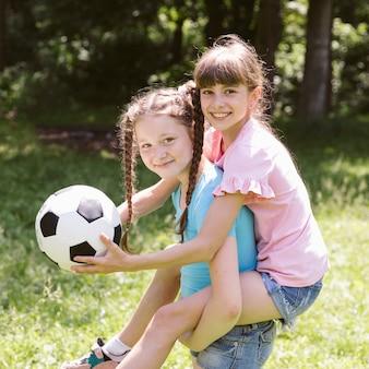 彼女の背中に彼女の友人によって運ばれている小さな女の子