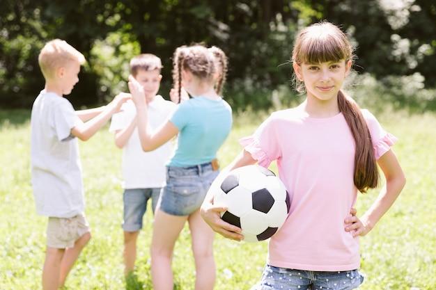 Маленькая девочка позирует с футбольным мячом