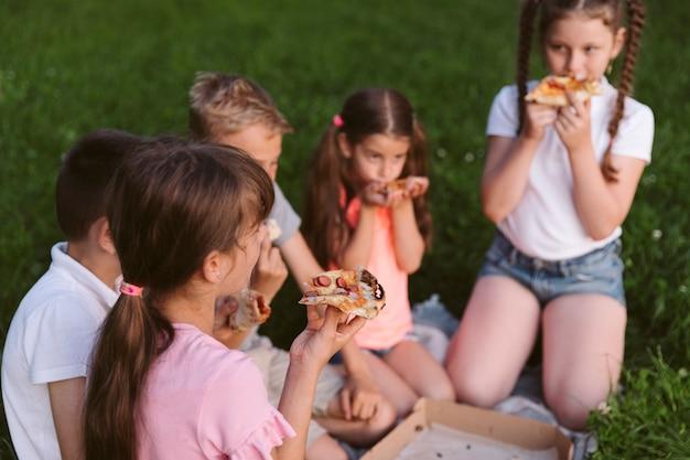 一緒にピザを食べている子供たち