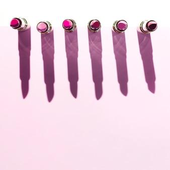 ピンクの背景に金属製の口紅の行