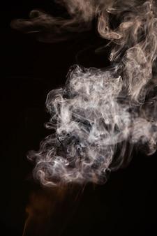 黒の背景に茶色の波状の煙