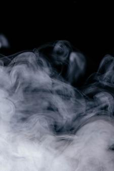 黒の背景に白の波状の煙