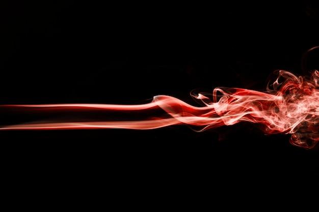黒の背景に赤い波状の煙