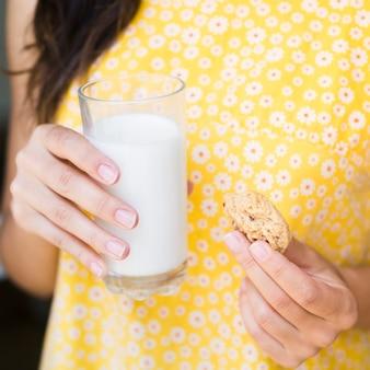 牛乳とクッキーのガラスを持つ女性