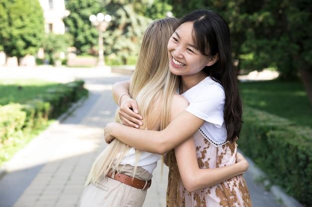 Вид спереди друзья обнимаются на открытом воздухе