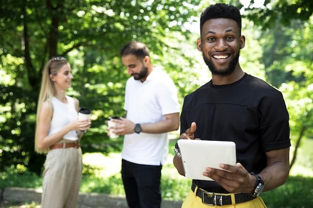 ミディアムショットのアフリカ人男性持株タブレット