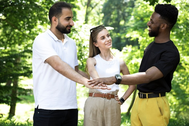 手を繋いでいる友人の正面の多様なグループ