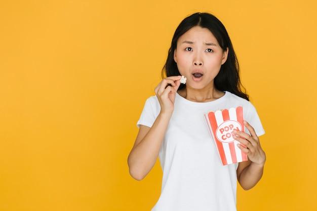 Шокированная женщина ест попкорн