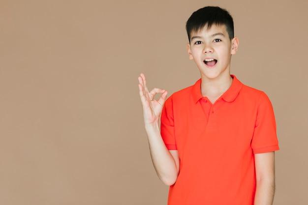 Мальчик показывает знак ок с копией пространства