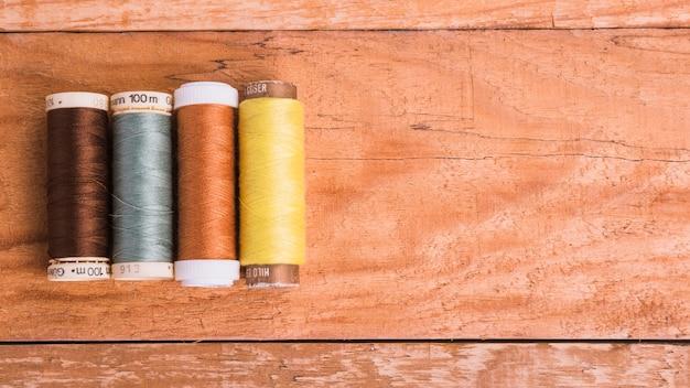 Линия катушки пряжи на деревянном фоне