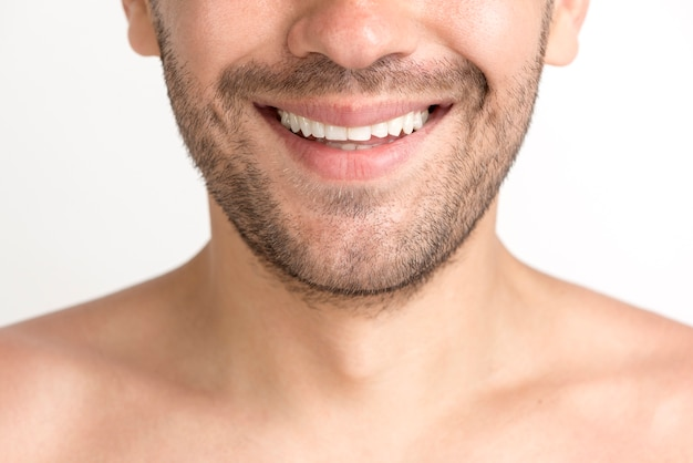 歯を見せる笑顔で無精ひげの若い男のクローズアップ