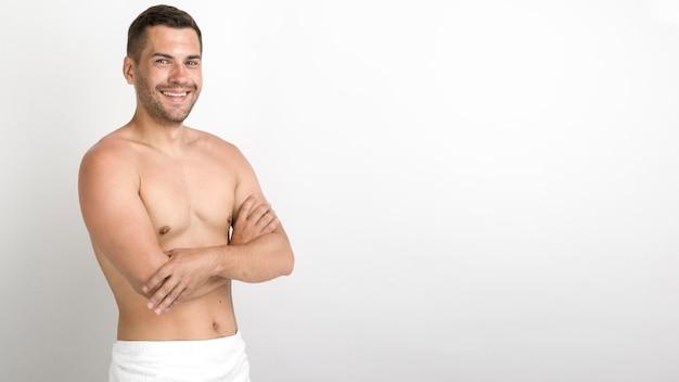 腕を組んで立っている上半身裸の若い男