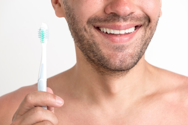 Крупный план улыбающегося молодого человека, держащего зубную щетку
