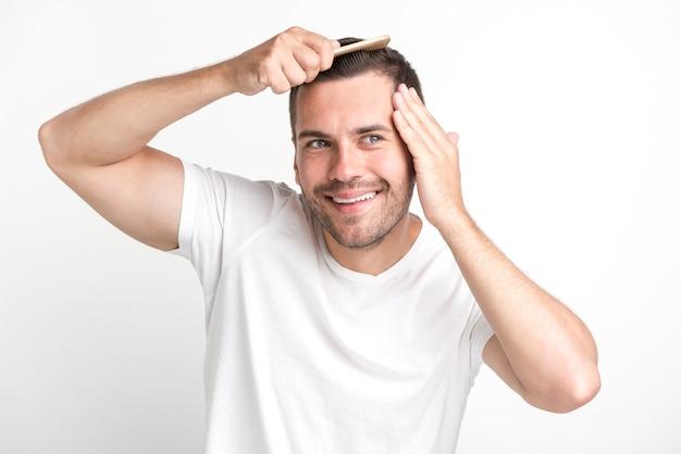 Улыбающийся человек в белой футболке расчесывает волосы, глядя в сторону