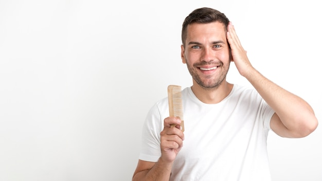 若い男持株櫛と白い背景に対して彼の髪を設定