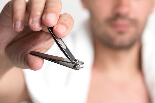 爪切りを持っている人間の手のクローズアップ