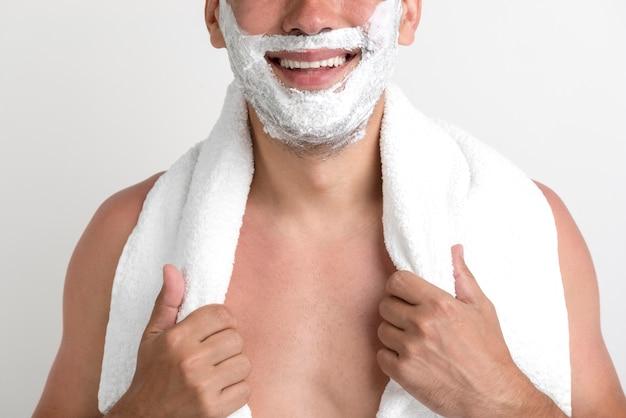 タオルを保持している彼の顔に泡を持つ男のクローズアップ