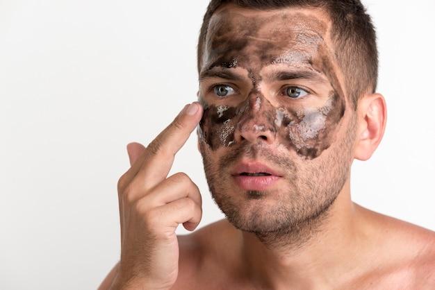 若い男が白い背景に対して彼の顔に黒いマスクを適用します。