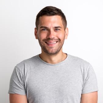 Портрет улыбающегося очаровательного молодого человека в серой футболке, стоящего на простом фоне