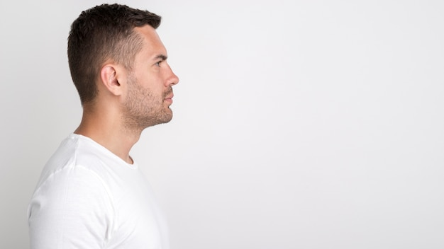 白い背景に対して立っている若い男の側面図