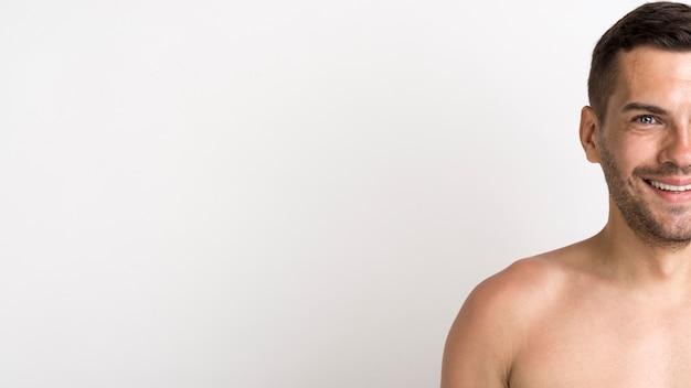 白い背景に対して立っている上半身裸の笑みを浮かべて若い男の半分の顔
