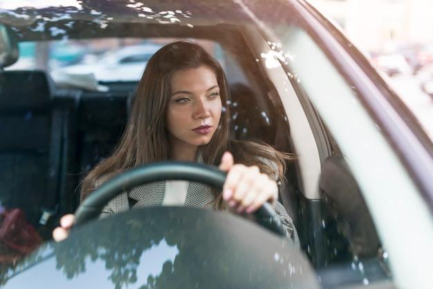 ビジネスの女性が車を運転