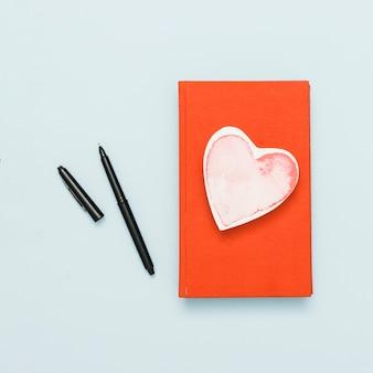 Вид сверху книги с карточкой в форме сердца