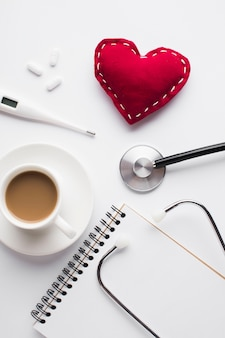 赤いグッズハートと机の上の医療アクセサリーとコーヒーのカップ