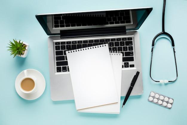 コーヒーカップと多肉植物の近くのラップトップ上のメモ帳の立面図、医療机の上