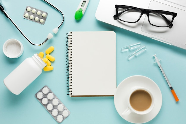 メモ帳付きのヘルスケア用品。一杯のコーヒーとテーブルの上のラップトップ上の眼鏡