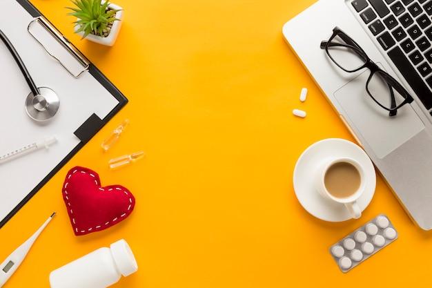 コーヒーカップと医師のデスクの平面図。黄色の背景のラップトップ