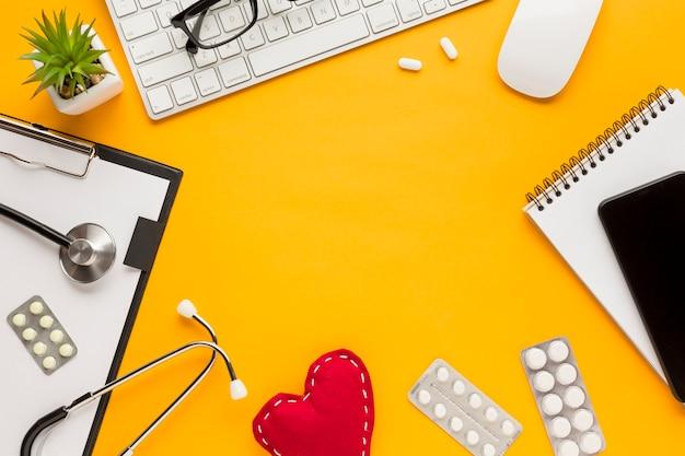 Вид сверху спирального блокнота; мобильный телефон; таблетки в блистерной упаковке; стетоскоп; буфер обмена и суккулент над желтым столом