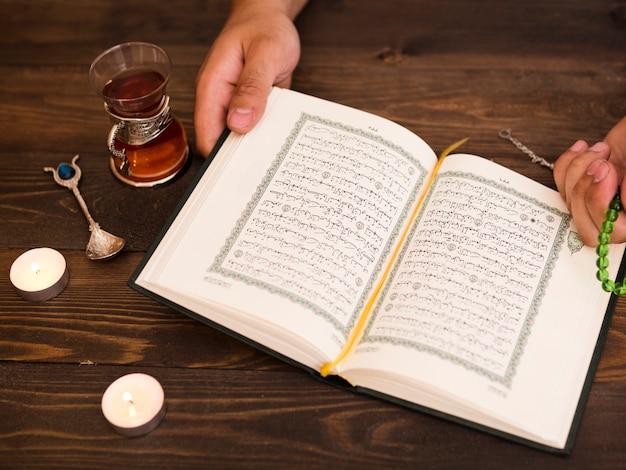 コーランを押しながら祈って手を閉じる