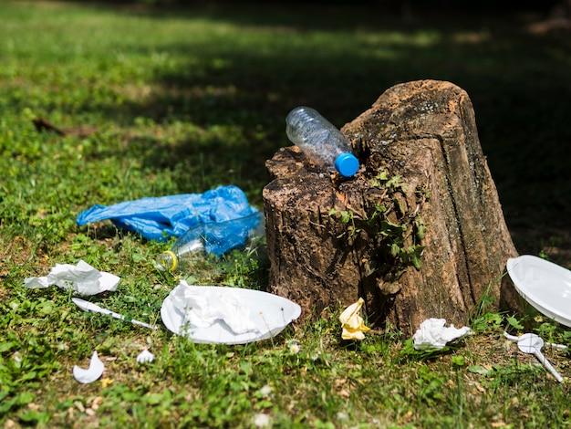 庭で木の切り株の近くのプラスチックゴミ