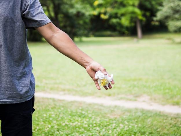 Конец-вверх руки человека бросая скомканную бумагу в парке