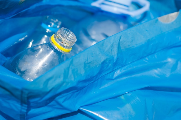 Крупным планом пластиковых бутылок в синий мусорный мешок