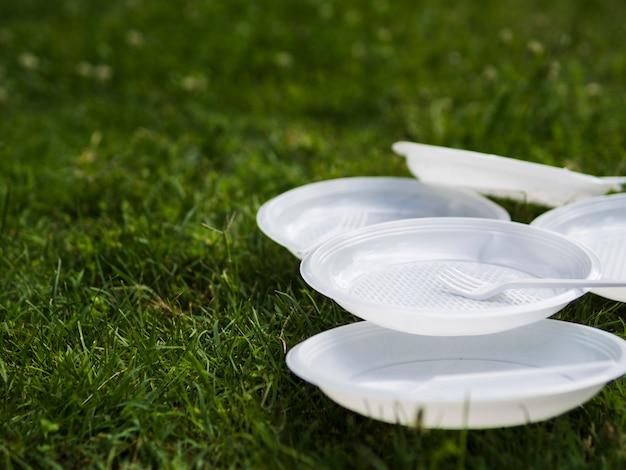 Крупный план белой пластиковой пластины и вилки на траве в парке